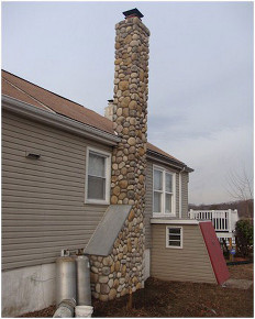 Stone chimney on side of house